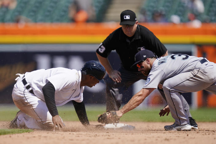 Detroit Tigers' Jonathan Schoop, left, safely beats the tag of Seattle Mariners second baseman Donovan Walton (31) as umpire Todd Tichenor looks on during the sixth inning of a baseball game, Thursday, June 10, 2021, in Detroit. (AP Photo/Carlos Osorio)
