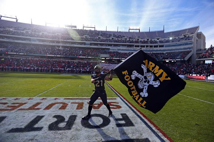 Army running back Zack Boobas waves an Army flag before the team's game against Houston at the 2018 Armed Forces Bowl at Amon G. Carter Stadium.