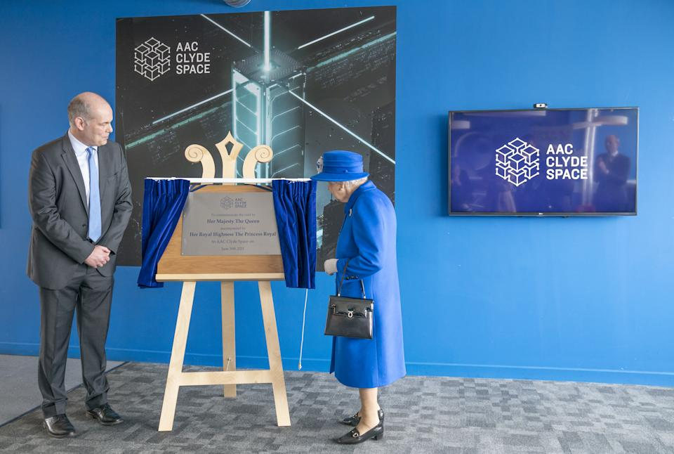 Queen Elizabeth II, who was accompanied by The Princess Royal, unveils a plaque in the offices of AAC Clyde Space during a visit to Skypark, Glasgow, to receive a briefing from the UK Space Agency and view satellite production, as part of her traditional trip to Scotland for Holyrood Week. Picture date: Wednesday June 30, 2021.