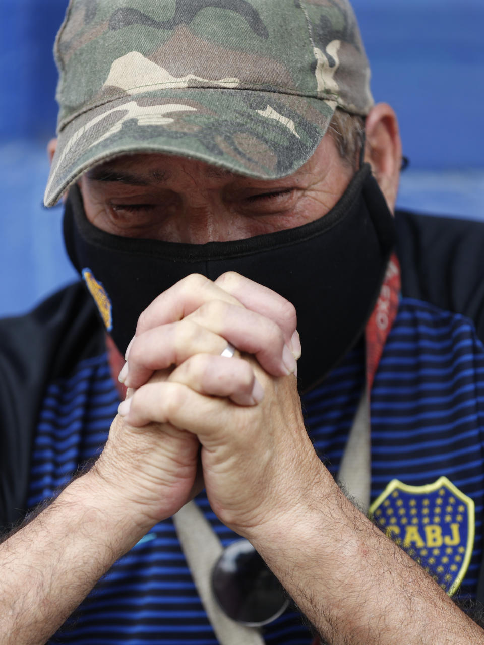 A fan mourns the death of Diego Maradona at the entrance of the Boca Juniors stadium known as La Bombomera, in Buenos Aires, Argentina, Wednesday, Nov. 25, 2020. The Argentine soccer great who was among the best players ever and who led his country to the 1986 World Cup title before later struggling with cocaine use and obesity, died from a heart attack on Wednesday at his home in Buenos Aires. He was 60. (AP Photo/Natacha Pisarenko)
