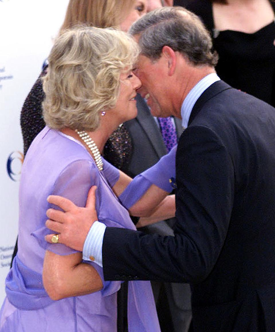 Britain's Prince Charles (R) kisses his companion Camilla Parker Bowles (L) at the National Osteoporosis Society's 15th Birthday Celebrations at Somerset House, London June 26, 2001. The party is hosted by Camilla, whose mother died of osteoperosis in 1994.    BR