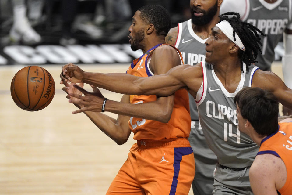 Los Angeles Clippers guard Terance Mann, right, knocks the ball from the hands of Phoenix Suns forward Mikal Bridges during the first half in Game 4 of the NBA basketball Western Conference Finals Saturday, June 26, 2021, in Los Angeles. (AP Photo/Mark J. Terrill)