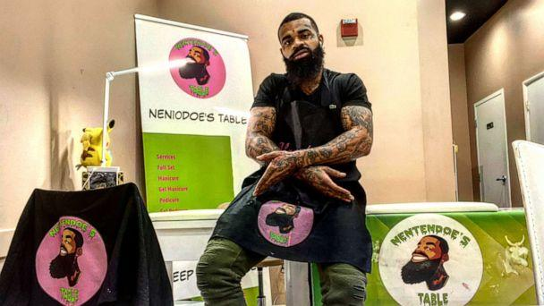 PHOTO: Atkins poses in front of his manicure table and T-shirts showcasing his business 'Nentendoe's Table.' (Courtesy Darnell Atkins)