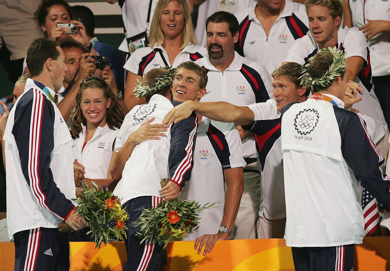 ATHENS - AUGUST 21:  Michael Phelps and Lenny Krayzelburg of the United States congratulate Ian Crocker and Jason Lezak of the United States relay team that won the gold medal and set a new world record of 3:30.68 in the men's swimming 4 x 100 metre medley relay competition on August 21, 2004 during the Athens 2004 Summer Olympic Games at the Main Pool of the Olympic Sports Complex Aquatic Centre in Athens, Greece.  Phelps and Krayzelburg will also receive gold medals for swimming the relay in the preliminaries. (Photo by Shaun Botterill/Getty Images)