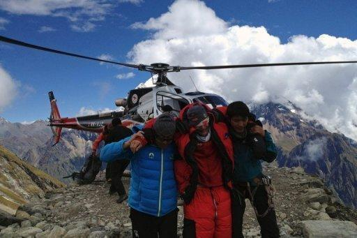 <p>Image provided by Simrik Air shows rescuers assisting a foreigner who was injured following an avalance at the Mount Manaslu base camp in Gorkha Districtst on September 23. Rescuers have scaled down a search for two French climbers and a Canadian missing in a Nepal avalanche which killed at least nine people attempting to scale one of the world's highest peaks.</p>