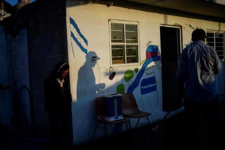 Central American migrants near a Honduran flag painted on a wall at the Sagrada Familia shelter in Mexico's Tlaxcala state as they make their way to the United States in April 2021