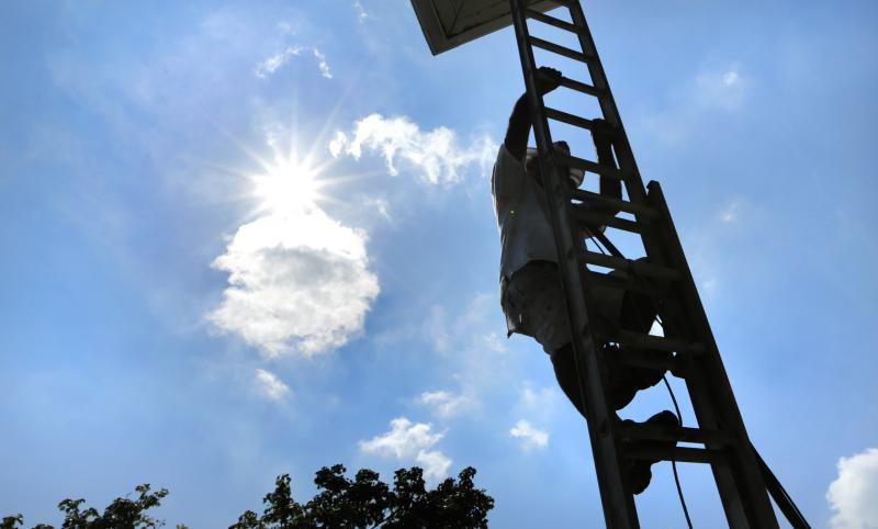 With the sun beating down, house painter Jesus Rubela climbs up a ladder while restoring a home in the South Boston neighborhood, Wednesday, July 17, 2013 in Boston. Temperatures in the Boston area reached the 90s, extending a heat wave. (AP Photo/Charles Krupa)
