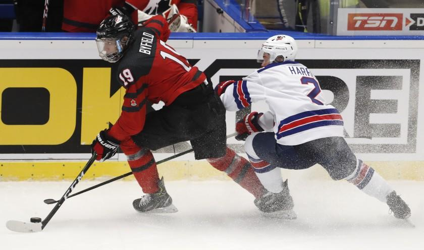 Jordan Harris of the US, right, challenges Canada's Quinton Byfield, left, during the U20 Ice Hockey Worlds match between Canada and the United States in Ostrava, Czech Republic, Thursday, Dec. 26, 2019. (AP Photo/Petr David Josek)