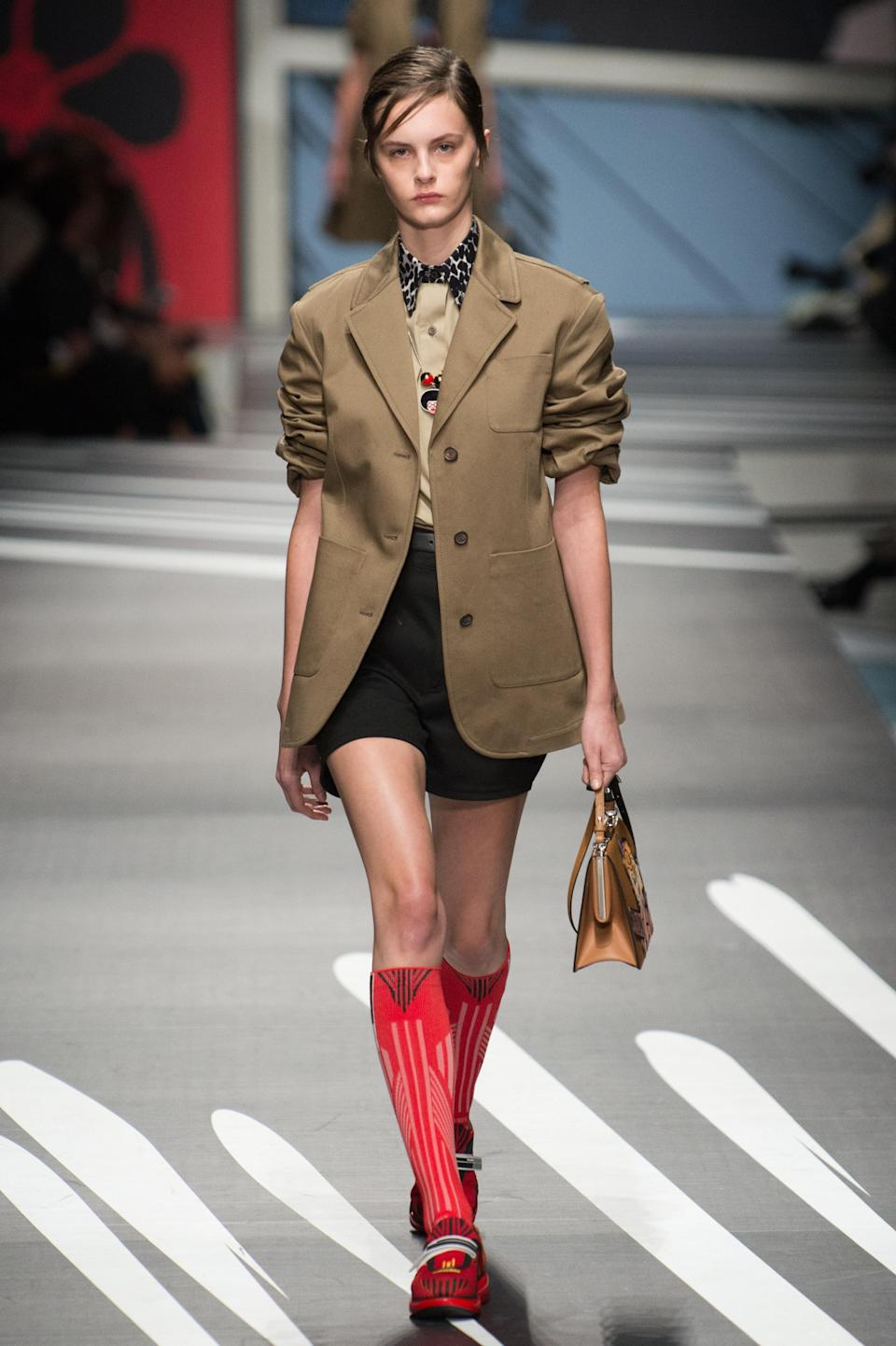 <p><i>Model wears a tan blazer, black shorts, and red knee-high socks from the SS18 Prada collection. (Photo: ImaxTree) </i></p>