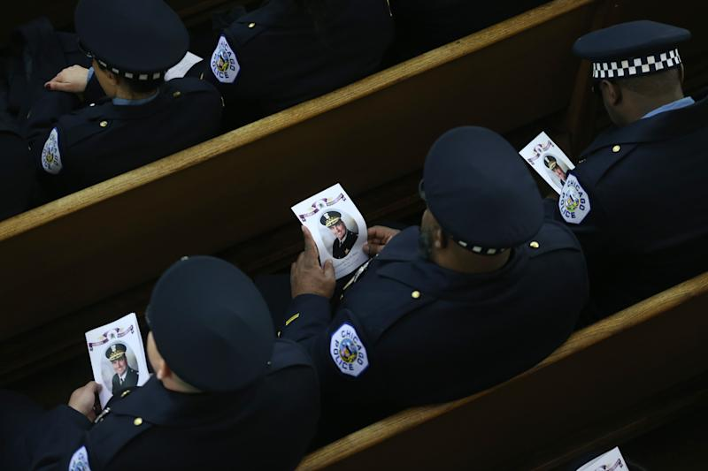 18th District Chicago police officers hold programs during the funeral mass for their slain commander, Chicago police Cmdr. Paul Bauer, at Nativity of Our Lord Roman Catholic Church on February 17, 2018 in Chicago, Illinois. Bauer was shot to death earlier in the week while confronting a suspect. (Photo by John J. Kim - Pool/Getty Images)