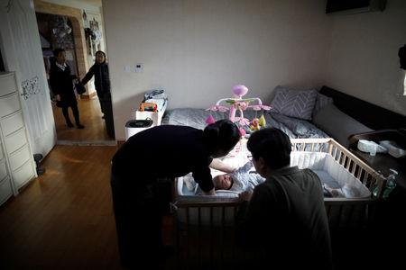 Lee Kyoung-min, a store manager at Lotte Mart, and his wife Kim Mi-sung take care of their baby son at their home in Seoul, South Korea, December 19, 2018. REUTERS/Kim Hong-Ji