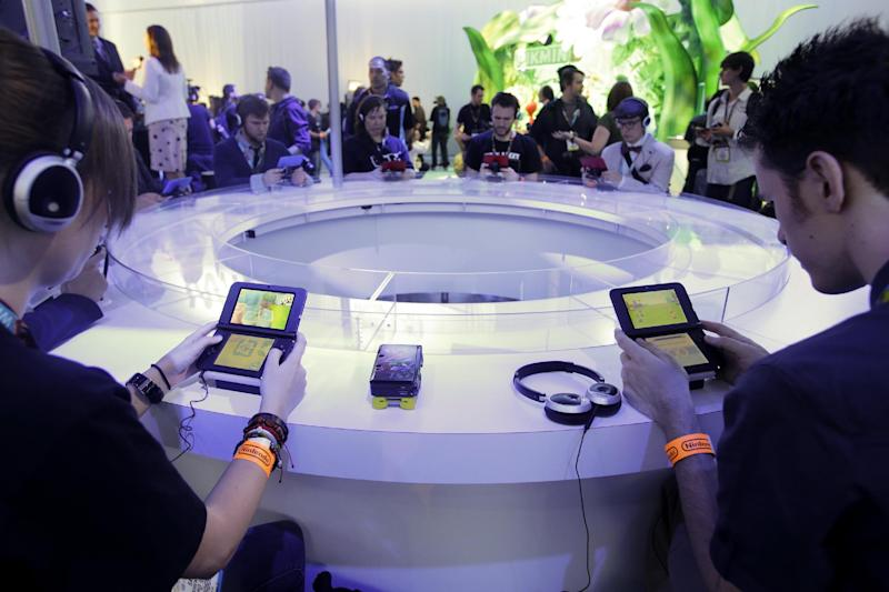 """FILE- In this June 11, 2013 file photo, attendees play video games on the Nintendo 3DS at the Nintendo Wii U software showcase during the E3 game show in Los Angeles. The gaming company said Tuesday, May 6, 2014, it wouldn't bow to pressure to allow players to engage in romantic entanglements with characters of the same sex in the English version of """"Tomodachi Life"""" following a social media campaign launched last month seeking virtual equality for the game's characters, which are modeled after real people. (AP Photo/Jae C. Hong, file)"""