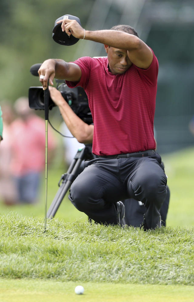 Tiger Woods wipes himself as he waits to play on the fourth hole during the final round of the Northern Trust golf tournament, Sunday, Aug. 26, 2018, in Paramus, N.J. (AP Photo/Mel Evans)