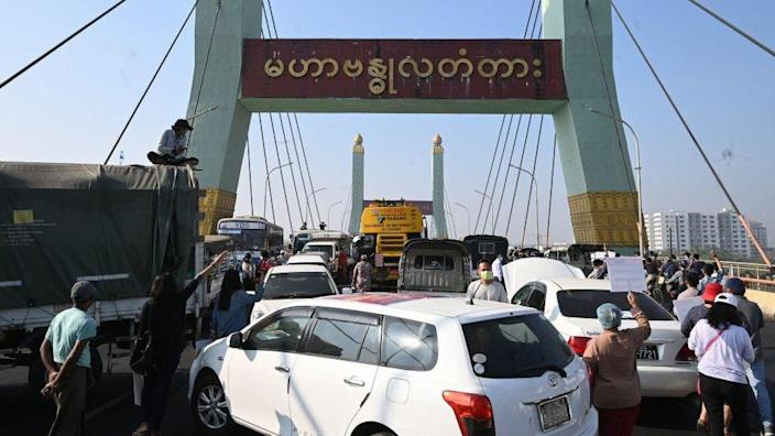 Protesters block a bridge with their cars during a demonstration against the military coup