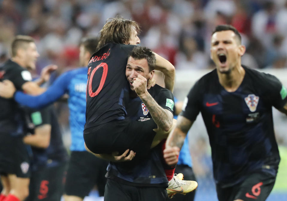 Croatia's Mario Mandzukic, center, carries Luka Modric when celebrating after his team advanced to the final during the semifinal match between Croatia and England at the 2018 soccer World Cup in the Luzhniki Stadium in Moscow, Russia, Wednesday, July 11, 2018. (AP Photo/Frank Augstein)
