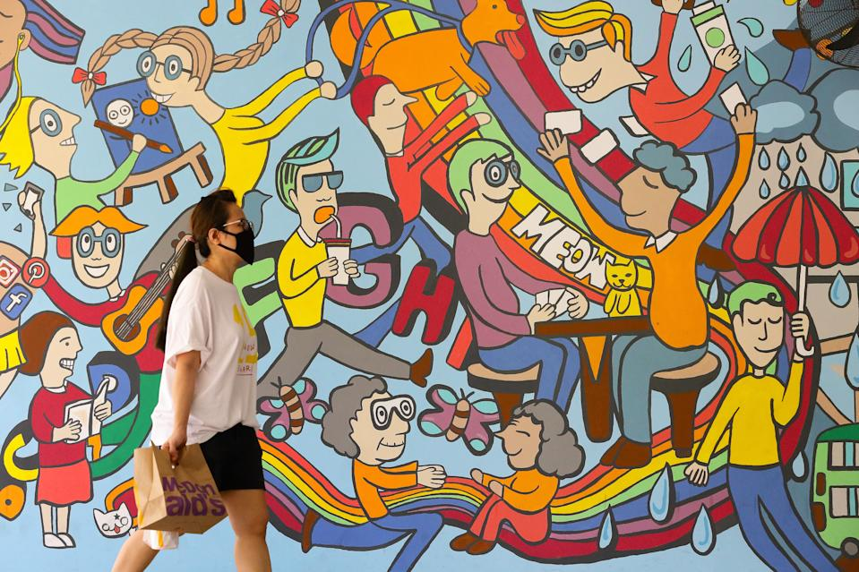 A woman wearing a protective mask walks past a wall mural on 31 May, 2020, in Singapore. (PHOTO: Getty Images file photo)