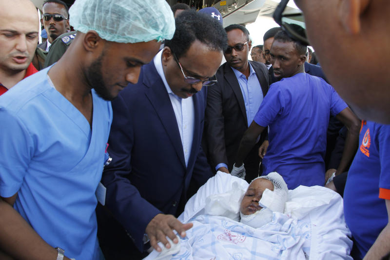 Somalia's President Mohamed Abdullahi Mohamed reacts with a wounded person to be airlifted to the Turkish capital for treatment after being injured in Saturday's car bomb blast in Mogadishu, Somalia, Sunday, Dec. 29, 2019.  A truck bomb exploded at a busy security checkpoint in Somalia's capital Saturday morning, killing at least 79 people including many students, authorities said. It was the worst attack in Mogadishu since the devastating 2017 bombing that killed hundreds. (AP Photo/Farah Abdi Warsameh)