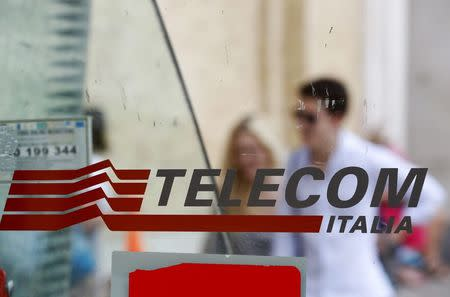 People walk past a Telecom Italia phone booth in Rome