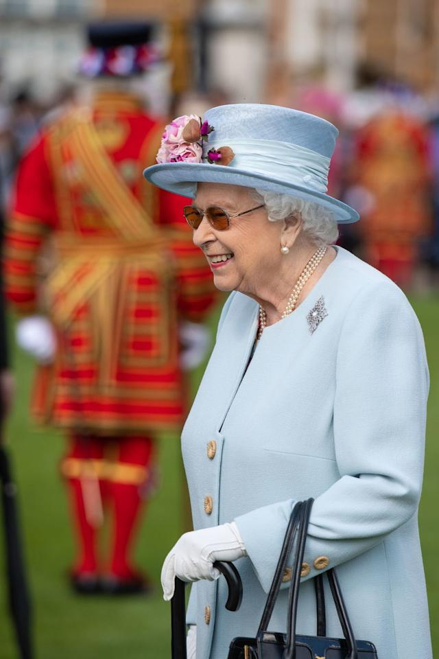 <p>The Queen arrives in a Stuart Parvin outfit and matching hat by Rachel Trevor Morgan.</p>