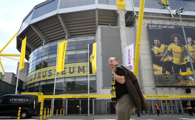 A supporter of Dortmund walks past the Signal Iduna Park before the German first division Bundesliga football match BVB Borussia Dortmund v Schalke 04 on May 16, 2020 in Dortmund, western Germany as the season resumed following a two-month absence due to the novel coronavirus COVID-19 pandemic. (Photo by INA FASSBENDER / AFP) (Photo by INA FASSBENDER/AFP via Getty Images)