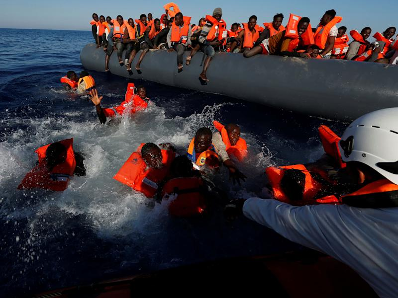 Migrants try to stay afloat after falling off their rubber dinghy during a rescue operation by Moas off the coast of Zawiya in Libya, on 14 April: Reuters