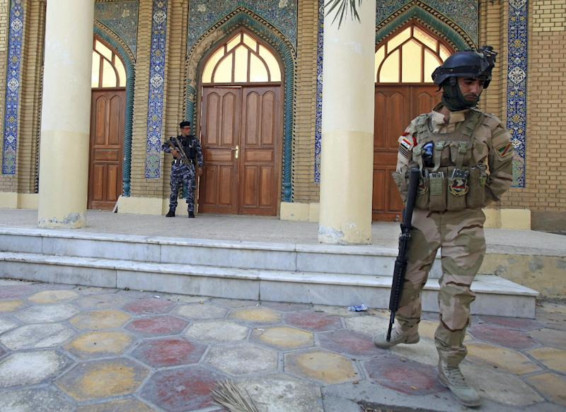 An Iraqi Army soldier, right, and a policeman, left, guard the Sunni Othman Mosque in Basra, 340 miles (550 kilometers) southeast of Baghdad, Iraq, Tuesday, Sept. 17, 2013. Gunmen have shot dead over a dozen Sunnis in Iraq's Shiite-majority city of Basra over the past two weeks, following threats to retaliate against them for attacks on Shiites in other parts of Iraq, police and a Sunni community leader say. (AP Photo/ Nabil al-Jurani)