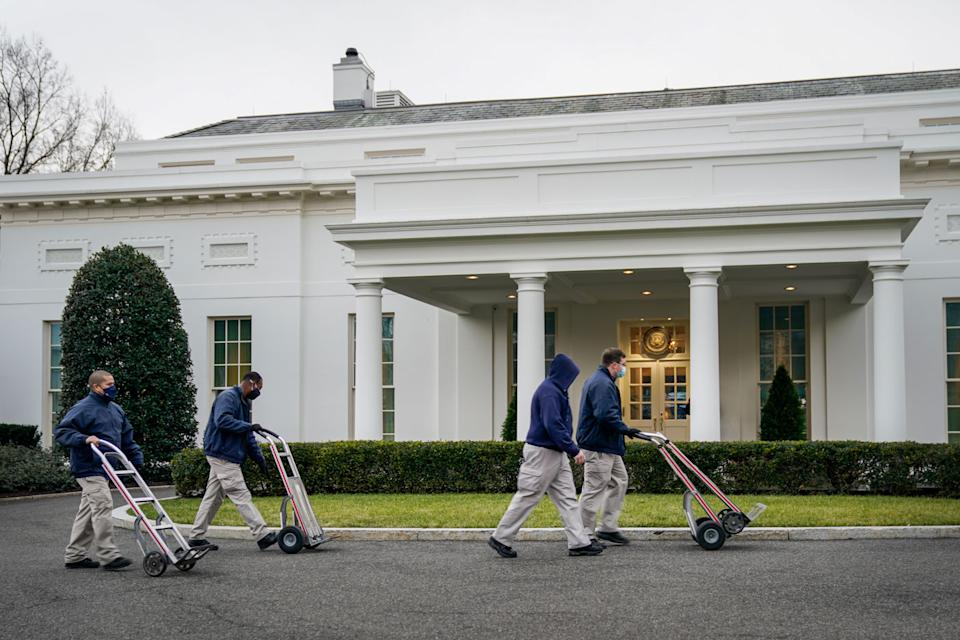 Pictured are people pushing moving trolleys outside the White House.