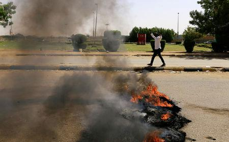 A Sudanese protester gestures as they burn tyres and barricade the road leading to al-Mek Nimir Bridge crossing over Blue Nile; that links Khartoum North and Khartoum, in Sudan May 13, 2019. REUTERS/Mohamed Nureldin Abdallah