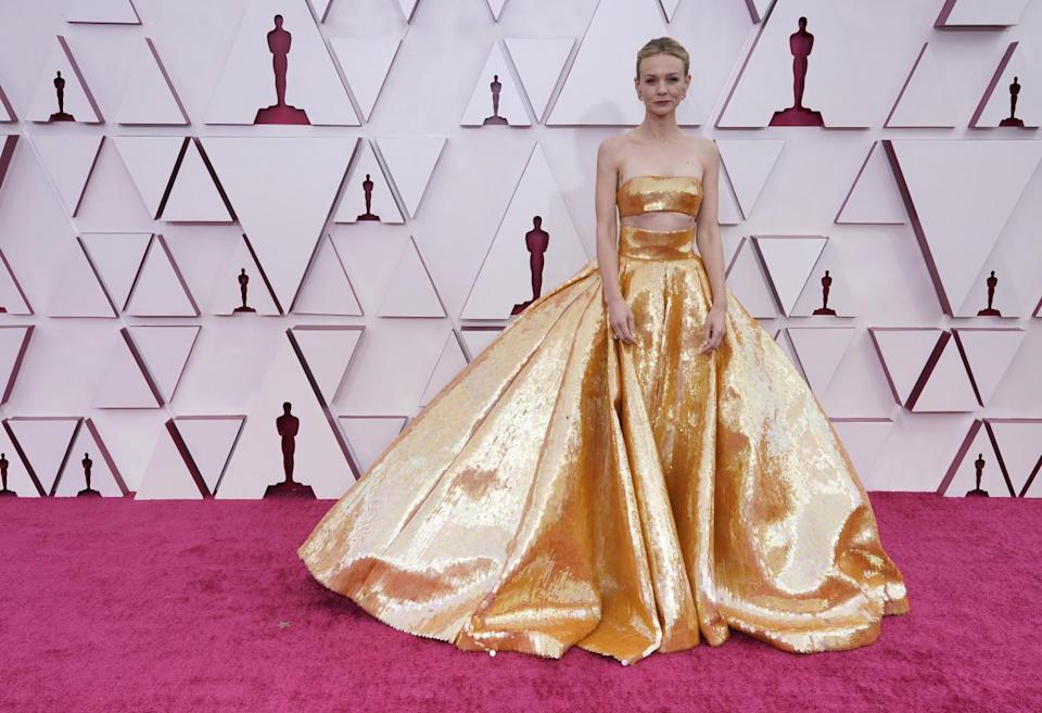 Carey Mulligan in a gold ballgown with a bandeau top.