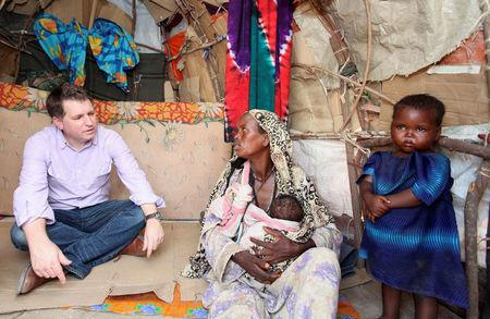 FILE PHOTO: Justin Forsyth, Chief Executive of Save the Children UK, talks to internally displaced Somalis at a camp in Hodan district of Somalia's capital Mogadishu, November 21, 2012. REUTERS/Feisal Omar/File Photo