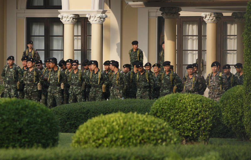 Soldiers stand guard at Government House in Bangkok, Thailand early Tuesday, Dec. 10, 2013. Prime Minister Yingluck Shinawatra dissolved Parliament's lower house on Monday and called early elections. But protesters seeking to topple her vowed to carry on their fight, saying they cannot win the polls because of corruption. (AP Photo/Greg Baker)