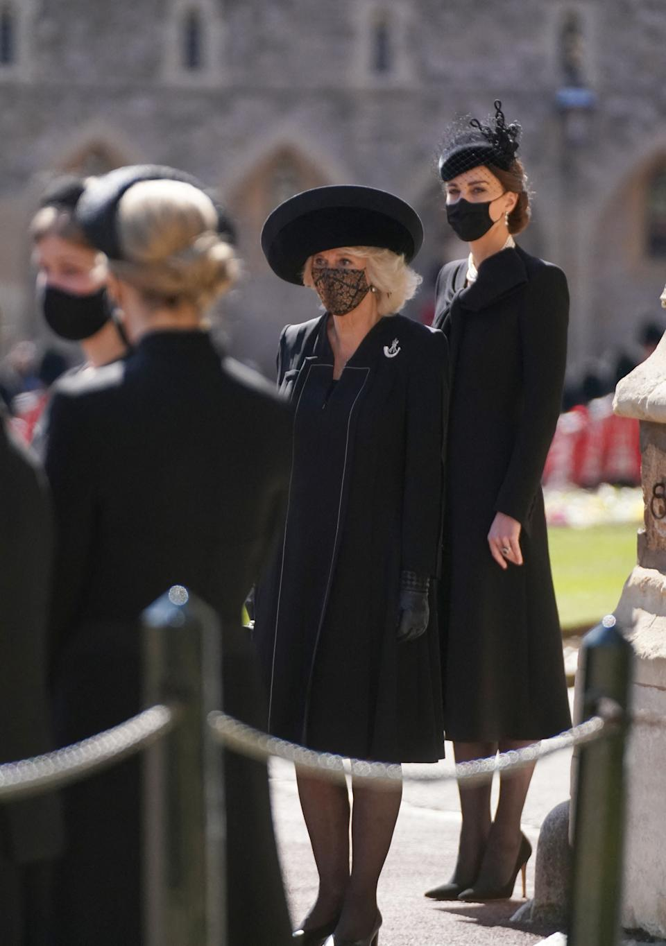 Duchess of Cambridge and Camilla stand outside St George's Chapel before the ceremonial funeral procession of Prince Philip