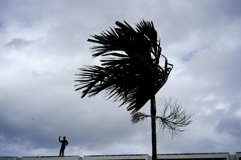 A man stands on a store's roof as he works to prepare it for the arrival of Hurricane Dorian in Freeport on Grand Bahama, Bahamas, Sunday, Sept. 1, 2019. | Ramon Espinosa—AP