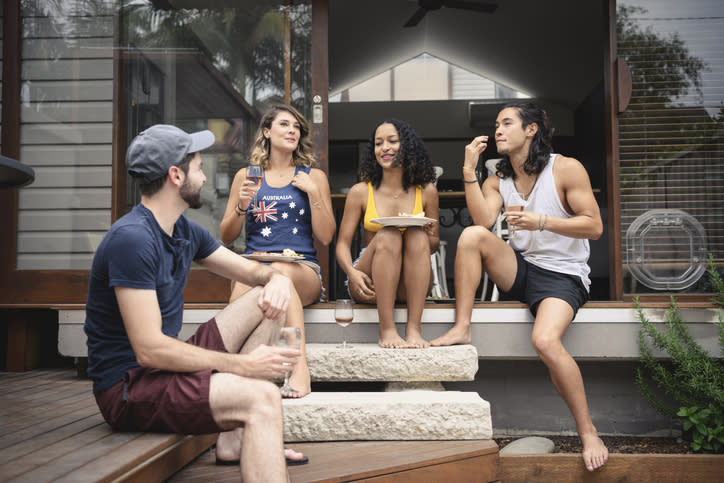 Adults sit on the back porch of a house enjoying drinks. Scott Morrison is reportedly set to allow up to 10 people to gather at a house.