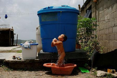 Luis Espinoza, 3, takes a bath next to a water tank, at his home in Charallave, Venezuela July 7, 2016. Luis's mother Oleydy Canizalez plans to have a sterilization surgery. REUTERS/Carlos Garcia Rawlins