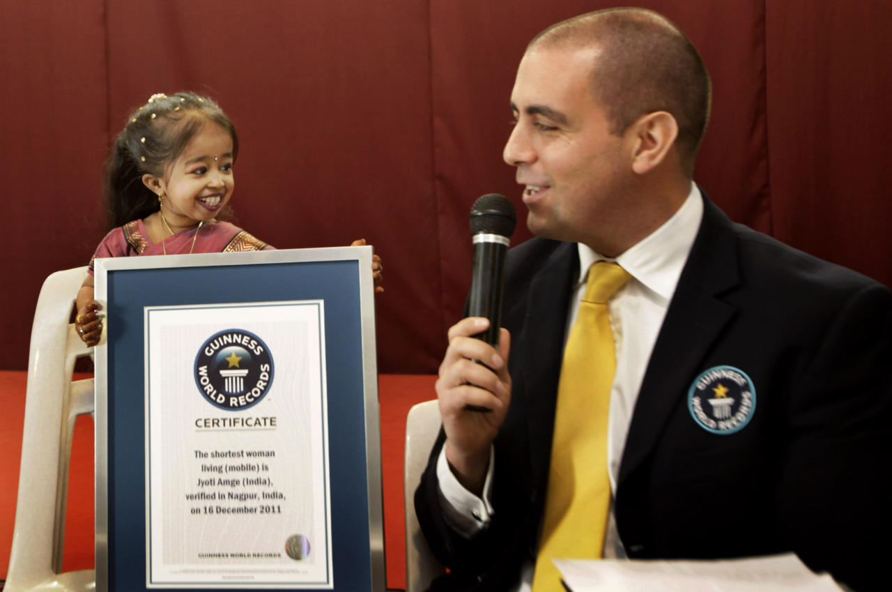 Guinness World Records adjudicator Rob Molloy, right, confers the title of the shortet woman of the world to Jyoti Amge, in Nagpur, India, Friday, Dec. 16, 2011. Amge was declared the shortest woman in the world measuring 62.8 centimeters (24.7 inches) by the Guinness World Records. (AP Photo/ Manish Swarup)