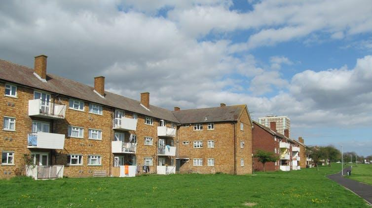 Landscape photograph of low block of flats with grass in front