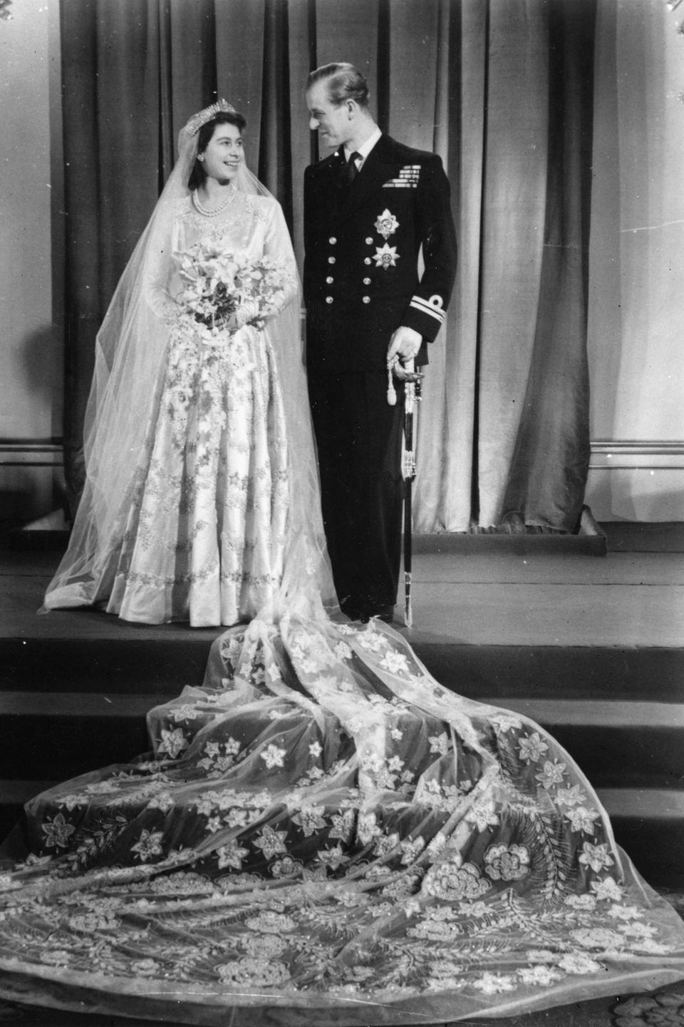 """<p>When Princess Elizabeth married Philip Mountbatten in 1947, she had to <a href=""""https://www.townandcountrymag.com/society/tradition/a13438510/queen-elizabeth-wedding-dress/"""" rel=""""nofollow noopener"""" target=""""_blank"""" data-ylk=""""slk:save up coupons to buy her dress"""" class=""""link rapid-noclick-resp"""">save up coupons to buy her dress</a>, as war rations were still in effect in the UK. That didn't stop the royal from looking stunning in a ivory silk and pearl gown. The couple was married in Westminster Abbey and have been married for 72 years now. </p>"""
