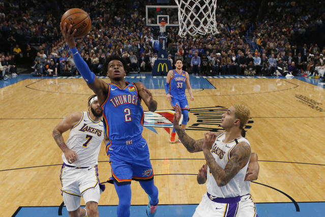 Oklahoma City Thunder guard Shai Gilgeous-Alexander (2) goes to the basket between Los Angeles Lakers center JaVale McGee (7) forward Kyle Kuzma, right, in the first half of an NBA basketball game Saturday, Jan. 11, 2020, in Oklahoma City. (AP Photo/Sue Ogrocki)