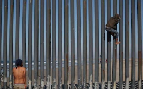 A migrant climbs the border fence between Mexico and the United States as another looks on in Tijuana - Credit: HANNAH MCKAY/REUTERS