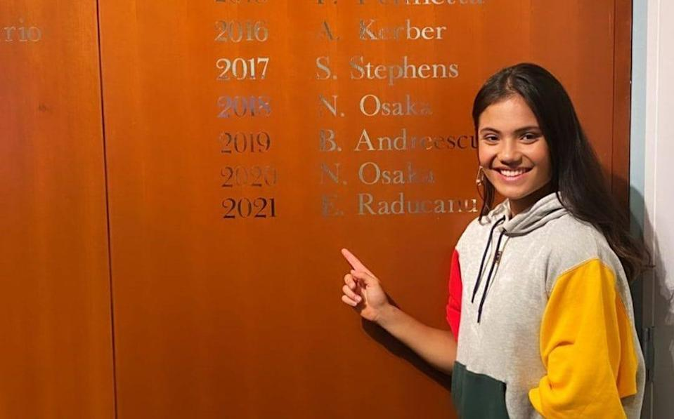 Raducanu points to her name engraved on the wall of US Open champions