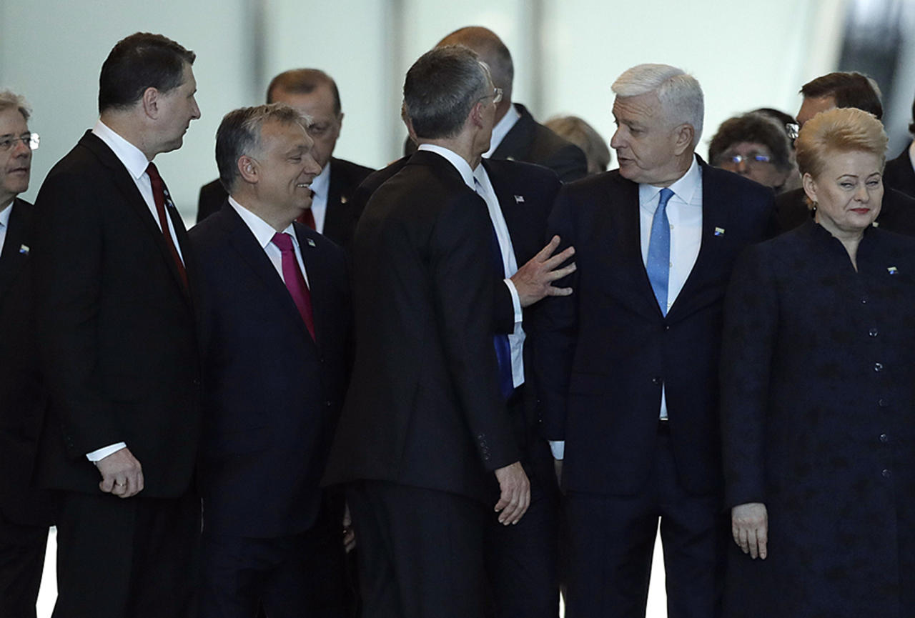 Montenegro Prime Minister Dusko Markovic, second right, appears to be pushed by Donald Trump, hidden behind NATO Secretary General Jens Stoltenberg, center, during a NATO summit of heads of state and government in Brussels on Thursday, May 25, 2017. US President Donald Trump inaugurated the new headquarters during a ceremony on Thursday with other heads of state and government. (AP Photo/Matt Dunham)