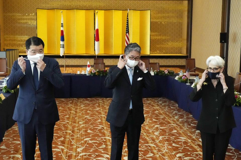 U.S. Deputy Secretary of State Wendy Sherman, right, South Korean First Vice Foreign Minister Choi Jong Kun, left, with Japanese Vice-Minister for Foreign Affairs Takeo Mori, center, take off their protective masks to pose for photographers prior to their trilateral meeting at the Iikura Guesthouse Wednesday, July 21, 2021, in Tokyo. (AP Photo/Eugene Hoshiko)