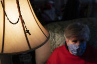 A rosary hangs on a lamp next to Donna Duval, 65, as she sits in her living room during a visit from Meals on Wheels in Pawtucket, R.I, Friday, Nov. 20, 2020. Meals on Wheels of Rhode Island has increased their home delivered meals across the state since the pandemic began from 1,200 to 4,000 meals per day. The organization has had 1,400 inquiries for joining the program since the start of the pandemic, that's well above the normal for a 7-month period. (AP Photo/David Goldman)