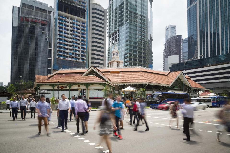 Singapore, Singapore - July 13, 2015: Office workers taking the pedestrian crossing going for lunch break at the Telok Ayer Market aka Lau Pa Sat.