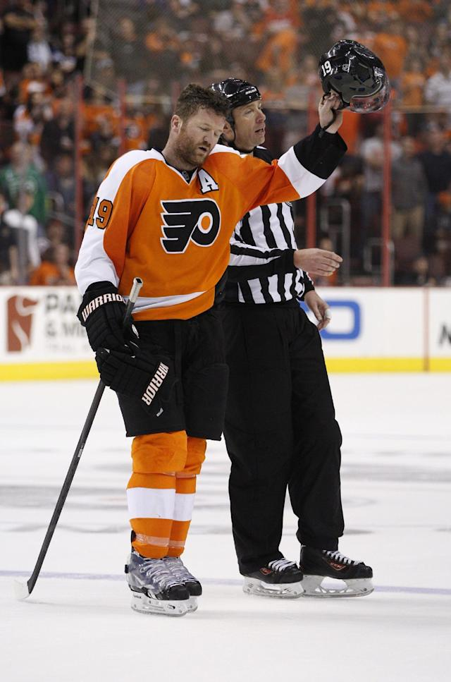 Philadelphia Flyers' Scott Hartnell-tips his helmet to the crowd as he is escorted off the ice by linesman Pierre Racicot, right, after receiving a five-minute penalty for spearing and a 10-minute game misconduct during the third period of an NHL hockey game against the Carolina Hurricanes, Sunday, April 13, 2014, in Philadelphia. The Hurricanes won 6-5 in a shootout. (AP Photo/Chris Szagola)