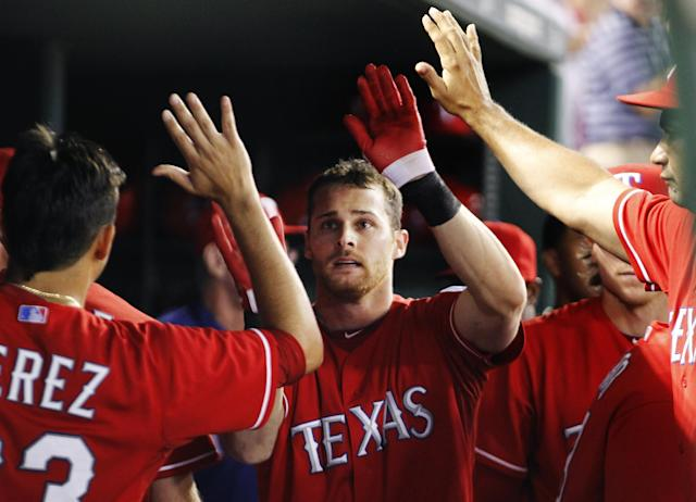 Texas Rangers' Craig Gentry celebrates after scoring on an Ian Kinsler single against the Tampa Bay Rays during the third inning of an American League wild-card tiebreaker baseball game Monday, Sept. 30, 2013, in Arlington, Texas. (AP Photo/Tim Sharp)