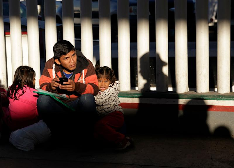 A migrant who did not give his name looks on with his children as they wait to hear if their number is called to apply for asylum in the United States, at the border Friday, Jan. 25, 2019, in Tijuana, Mexico. The Trump administration on Friday will start forcing some asylum seekers to wait in Mexico while their cases wind through U.S. courts, an official said, launching what could become one of the more significant changes to the immigration system in years. (AP Photo/Gregory Bull)
