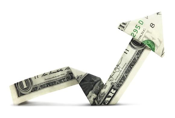 A dollar bill folded as an arrow that goes down but then back up higher.