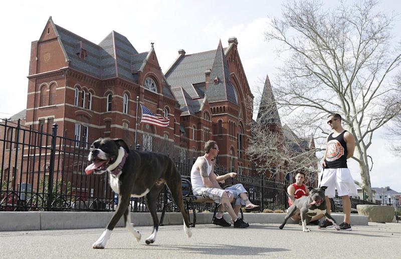 This April 10, 2013 photo shows dog owners chatting while their pets roam around the dog park located across from Music Hall at Washington Park in Cincinnati's Over-the-Rhine neighborhood. This picturesque neighborhood was named and settled by German immigrants in the 19th century, (AP Photo/Al Behrman)